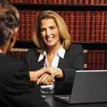 female attorney shaking hand of male by computer